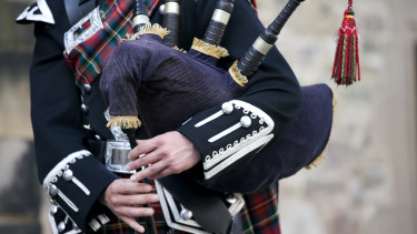 a Scottish bagpiper clad in a traditional scottish tartan playing the Scottish bagpipe