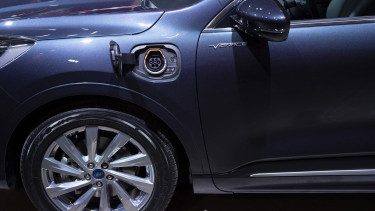 An electrical charging port sits on the bodywork of a Kuga Vignale hybrid automobile displayed during a Ford Motor Co. launch event in Amsterdam, Netherlands, on April 2, 2019.