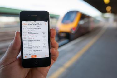Egy ember egy régi iPhone-on szemléli a vonatmenetrendet, miközben a háttérben egy vonat áll be a pályaudvarra. Fotó: Shutterstock