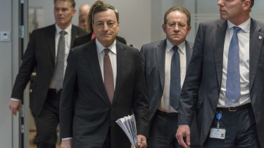 European Central Bank president Mario Draghi (L) and ECB vice president Vitor Constancio (C) arrive to give their press conference in the ECB Headquarters in Frankfurt, Germany