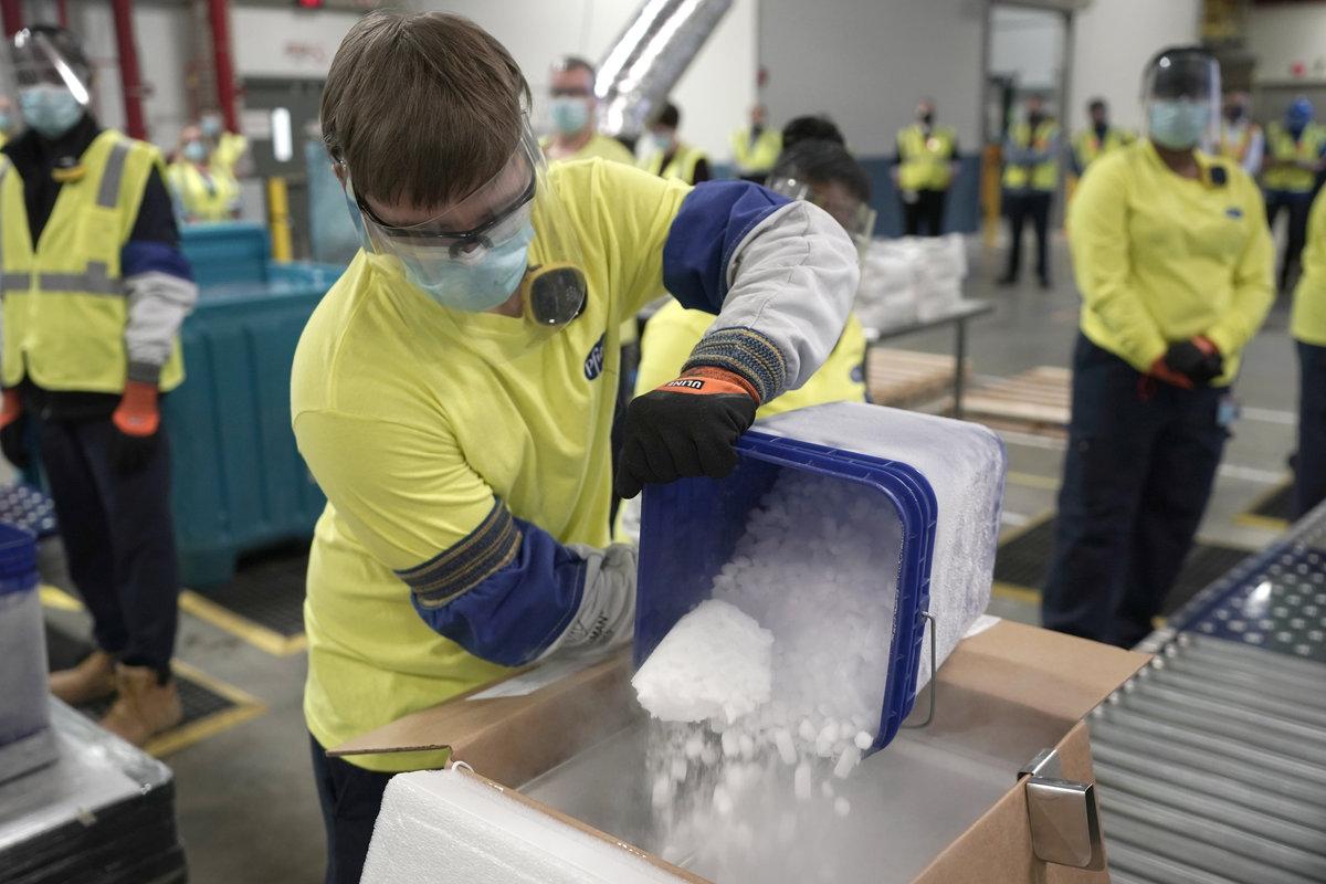 Szárazjeget öntenek egy dobozba, miközben a Pfizer és a BioNTech vállalatok koronavírus ellen közösen kifejlesztett oltóanyagát csomagolják az amerikai Pfizer gyárában, a Michigan állambeli Portage-ben 2020. december 13-án, amikor megkezdik a szérum első adagjainak kiszállítását az Egyesült Államokban. MTI/EPA/AP pool/Morry Gash