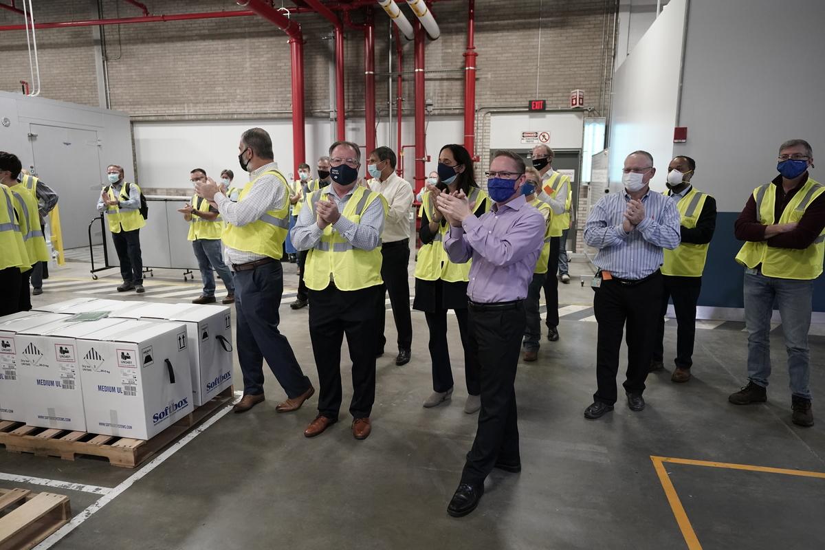 Tapsolnak a dolgozók, miután befejezték az oltóanyagok csomagolását az amerikai Pfizer gyárában. Morry Gash - Pool/Getty Images
