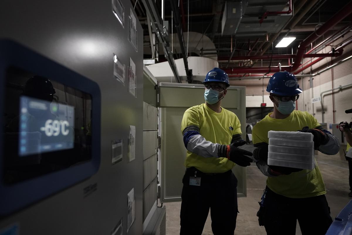 A fagyasztóláda hőmérője -69 Celsius-fokot mutat, közben a vakcinát készítik elő a szállításra. Morry Gash - Pool/Getty Images