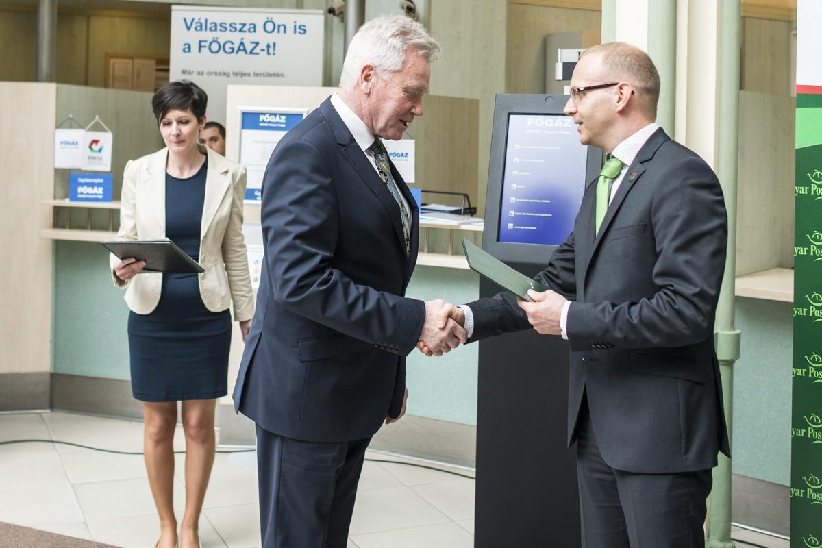 Laczó Sándor, a FŐGÁZ Zrt. vezérigazgatója és Szarka Zsolt, a Magyar Posta Zrt. vezérigazgatója (j) a nemzeti közszolgáltatás hazai ügyfélszolgálati hálózatának átadásán a pécsi 1-es postán 2015. április 2-án. Bejelentették, hogy április 1-jén megkezdte működését az Első Nemzeti Közműszolgáltató Zrt. (ENKSZ) a gázüzletágban. Kép forrása: MTI Fotó, Marjai János